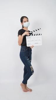 Une adolescente ou une jeune femme asiatique porte un masque facial et une main tenant un panneau de clapet ou une ardoise de film dans la production vidéo, le cinéma, l'industrie du cinéma sur fond blanc.
