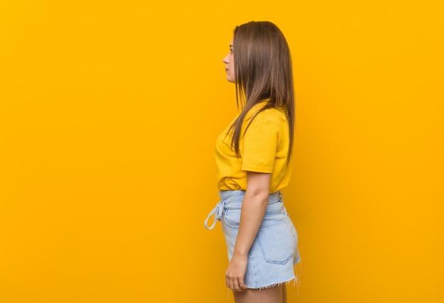 Adolescente jeune femme vêtue d'une chemise jaune, regardant à gauche, pose sur le côté