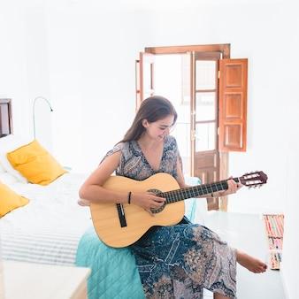 Adolescente jouant de la guitare dans la chambre