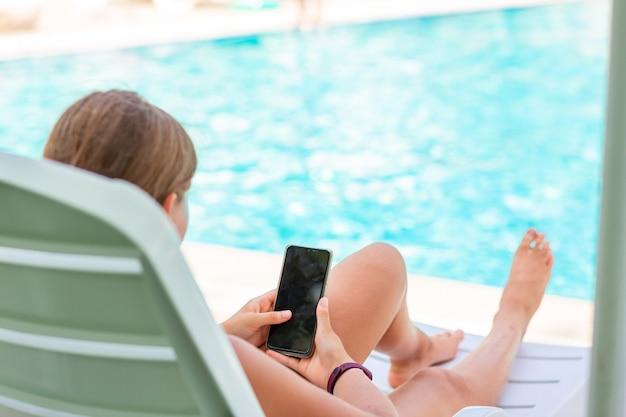 Adolescente jouant à des jeux et recherchant le web au téléphone à la piscine en vacances