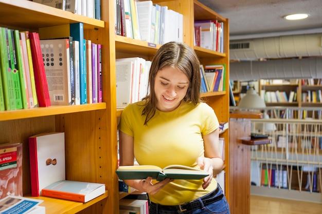 Adolescente joyeuse, appréciant la lecture près de la bibliothèque
