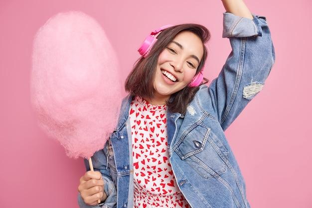 Une adolescente joyeuse incline la tête et lève le bras s'amuse à écouter de la musique via des écouteurs sans fil vêtus d'une veste en jean à la mode et contient de la barbe à papa sucrée isolée sur un mur rose. mode de vie des gens