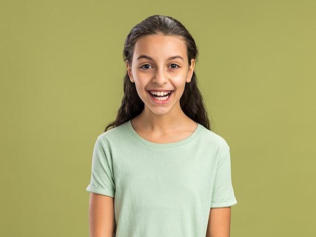 Adolescente joyeuse regardant l'avant en riant isolé sur un mur vert olive
