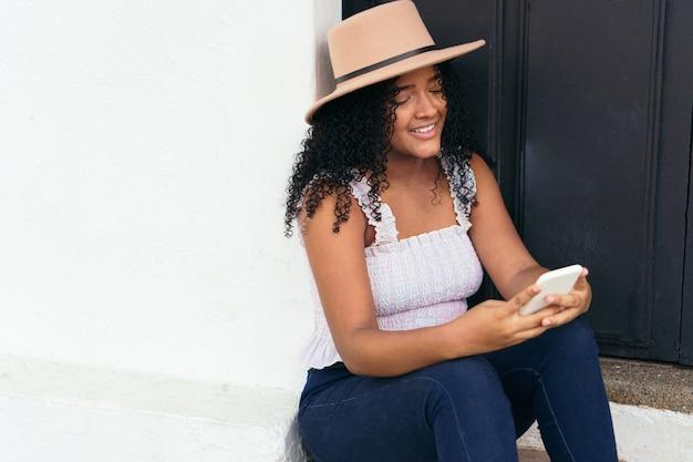 Une adolescente latina vérifiant son téléphone