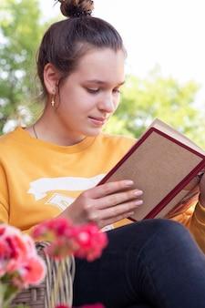 Adolescente lit un livre dans le jardin
