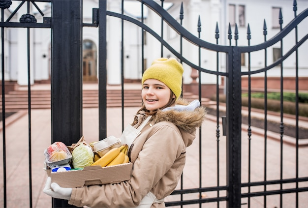 Une adolescente livre des courses à une personne âgée, pendant l'épidémie de coronovirus.