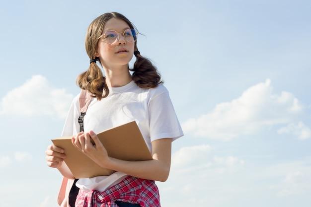 Adolescente avec livre de lecture de sac à dos