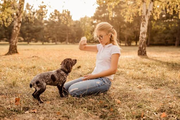 Adolescente avec des lunettes jouant sur l'herbe avec son petit chien