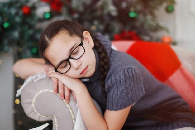 Une adolescente à lunettes avec des nattes est assise près d'un fauteuil d'arbre de noël et regarde la caméra.