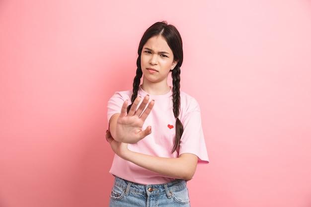 Adolescente malheureuse avec deux tresses rejetant et montrant un geste d'arrêt à l'avant isolé sur un mur rose