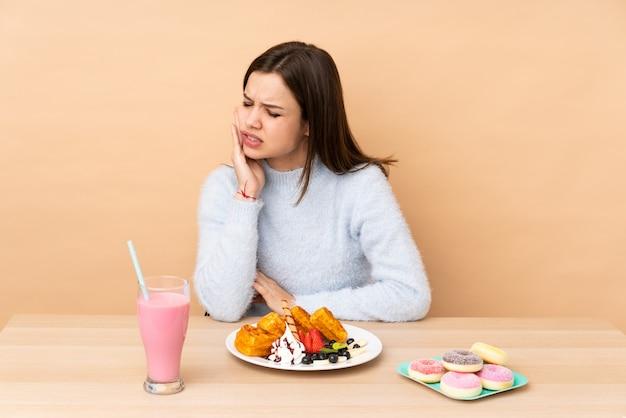 Adolescente, manger des gaufres sur beige avec maux de dents