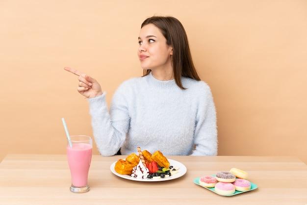 Adolescente, manger des gaufres sur un doigt pointé beige sur le côté et présenter un produit