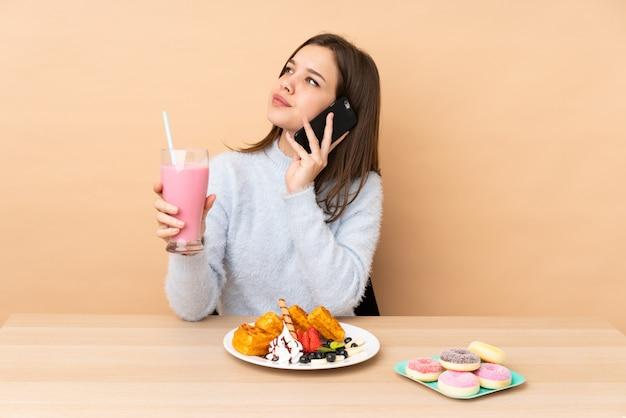Adolescente, manger des gaufres sur un mur beige tenant du café à emporter et un mobile