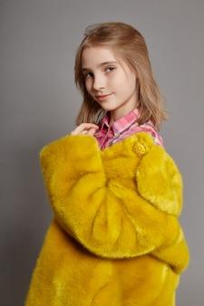 Adolescente en manteau de fausse fourrure jaune, portrait