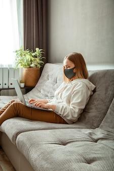 Une adolescente masquée fait un apprentissage en ligne via un ordinateur portable covid 19 temps de verrouillage. travail à distance pendant la pandémie de coronavirus. une femme portant un masque de protection travaille avec un ordinateur portable au bureau à domicile, assise sur un canapé.