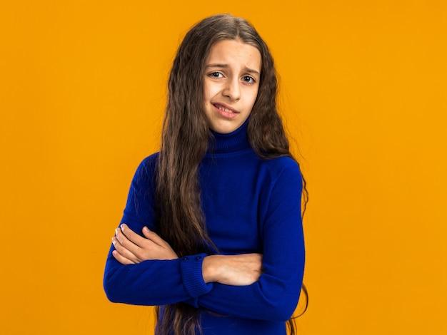 Adolescente mécontente debout avec une posture fermée regardant l'avant isolé sur un mur orange avec espace de copie