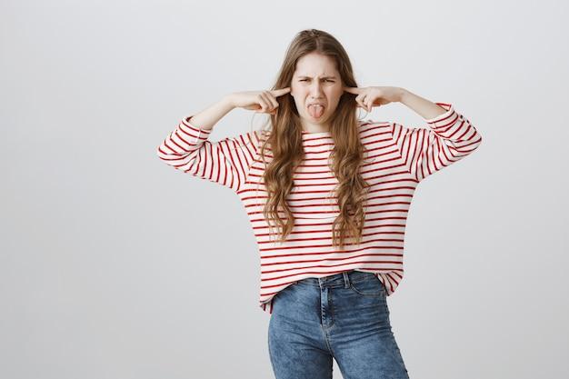 Une adolescente mécontente et dérangée ferme les oreilles du bruit affreux et montre la langue
