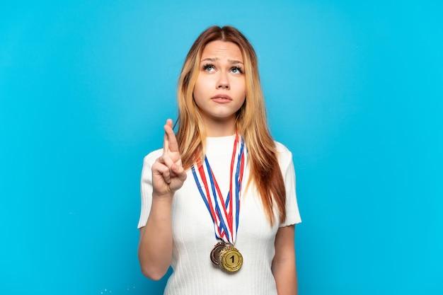 Adolescente avec des médailles sur fond isolé avec les doigts croisés et souhaitant le meilleur