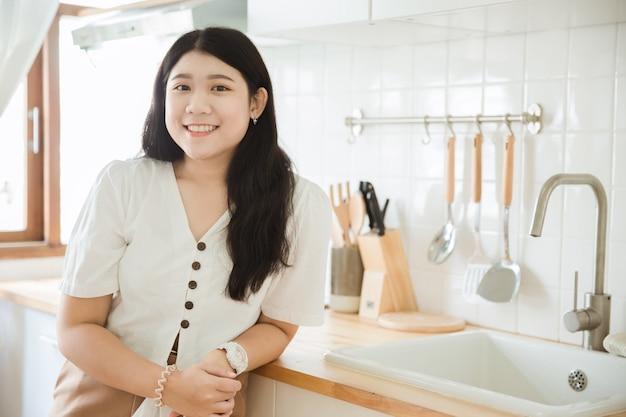 Adolescente mignonne asiatique souriant dans la cuisine pour la jeune femme au foyer en asie