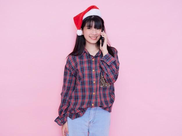 Adolescente mignonne en bonnet de noel avec smartphone sur mur rose. espace pour le texte