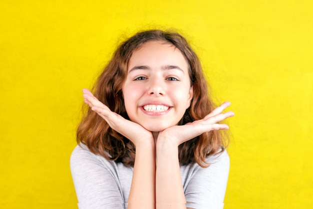 Adolescente mignonne avec une grimace souriante. paumes sur les joues