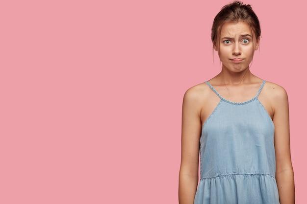 Une adolescente mignonne insatisfaite a une expression faciale agacée, fronce les sourcils et serre les lèvres