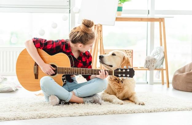 Adolescente mignonne jouant de la guitare avec un beau chien à l'intérieur