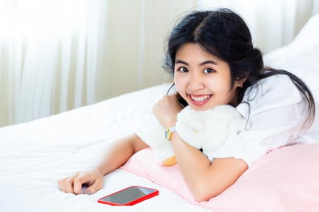 Adolescente mignonne joyeuse avec smartphone sur lit