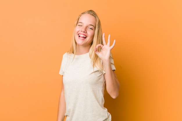 Adolescente mignonne et naturelle fait un clin d'œil et tient un geste correct avec la main.