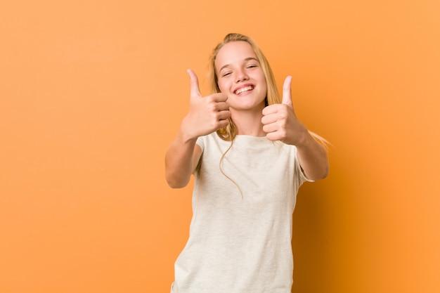 Adolescente mignonne et naturelle avec les pouces vers le haut, applaudit à quelque chose, soutient et respecte le concept