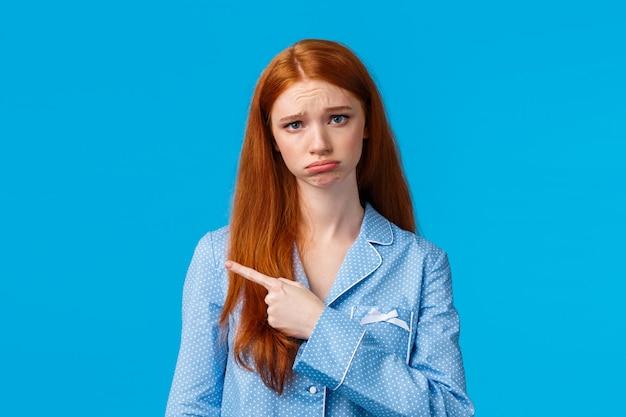 Adolescente mignonne stupide et timide bouleversée aux cheveux longs rouges portant des vêtements de nuit, bouder et froncer les sourcils triste