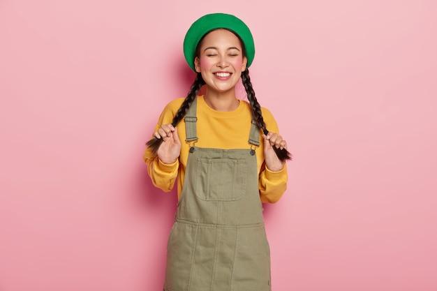 Adolescente modeste mignonne tient deux nattes, profite d'un moment de vie positif, porte un béret vert et un sarafan, a un piercing au nez