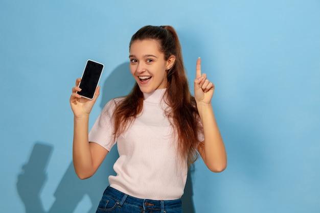 Adolescente montrant l'écran du téléphone, pointant vers le haut