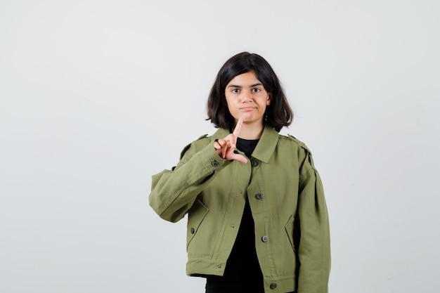Une adolescente montrant un signe de perdant en t-shirt, une veste et l'air insatisfait. vue de face.