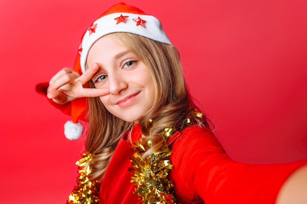 L'adolescente montre un geste de salutation et prend un selfie dans le chapeau du père noël