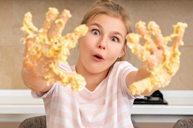 Adolescente montre les mains sales dans la pâte s'amuser dans la cuisine