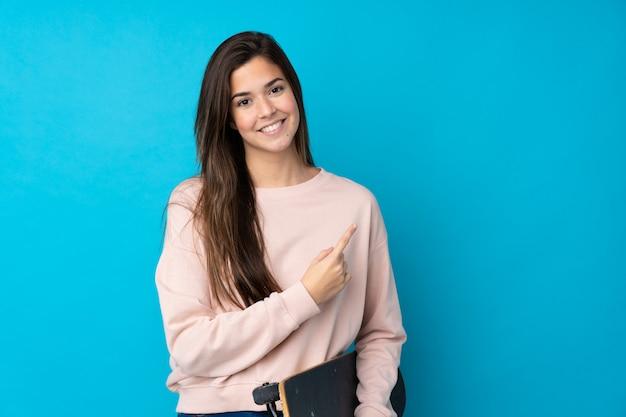 Adolescente sur mur bleu isolé avec un patin et pointant vers le côté