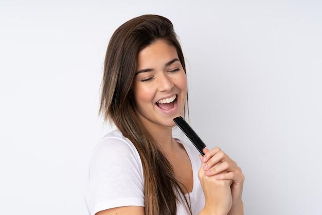 Adolescente sur mur isolé avec peigne à cheveux et chant