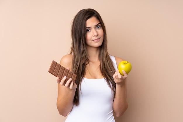 Adolescente sur mur isolé en prenant une tablette de chocolat dans une main et une pomme dans l'autre