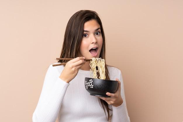Adolescente sur mur isolé tenant un bol de nouilles avec des baguettes et le manger