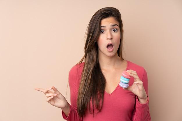 Adolescente sur mur isolé tenant des macarons français colorés et pointant le côté