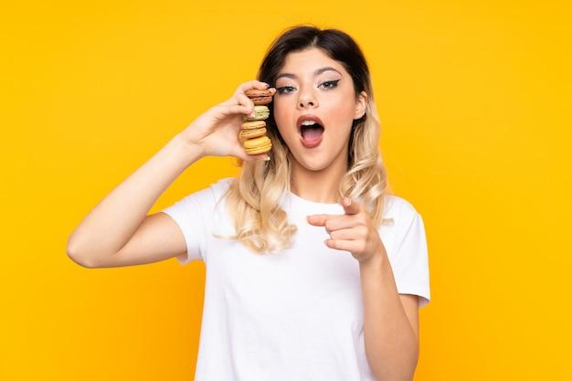 Adolescente sur mur jaune tenant des macarons français colorés et surpris tout en pointant devant