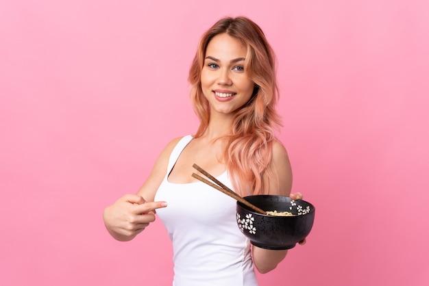 Adolescente sur mur rose isolé et le pointant tout en tenant un bol de nouilles avec des baguettes