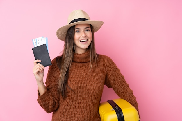 Adolescente sur mur rose isolé en vacances avec valise et passeport