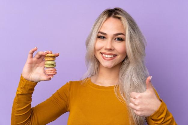 Adolescente sur mur violet tenant des macarons français colorés avec les pouces vers le haut