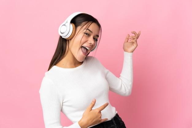 Adolescente sur la musique d'écoute bleue et faisant le geste de la guitare