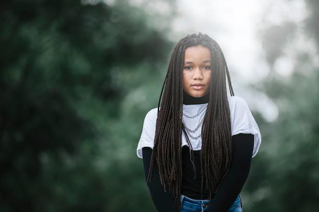 Adolescente noire aux cheveux tressés, expression sérieuse dans un parc