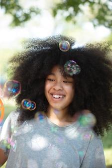 Adolescente noire mignonne jouant avec des bulles de savon
