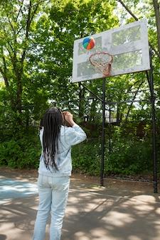 Adolescente noire souriante jouant au basket-ball