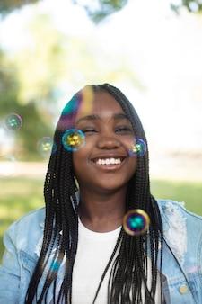 Adolescente noire souriante jouant avec des bulles de savon